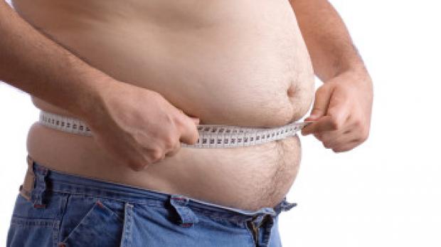 fat man holding a measurement tape