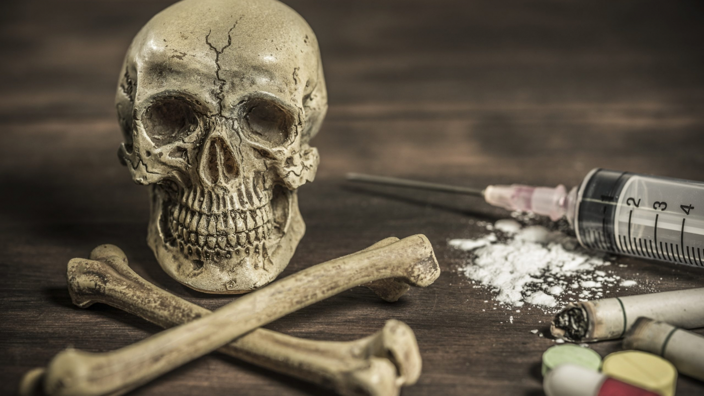 Human skull and crossbones with drug addict, healthcare and medical drugs addition concept