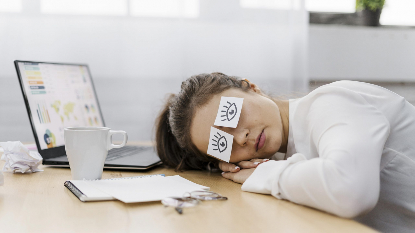 tired-businesswoman-covering-her-eyes-with-drawn-eyes-paper