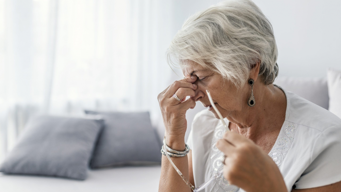 Mature woman sitting on a white sofa in a home touching her head with her hands while having a headache pain and feeling unwell. Senior woman with headache