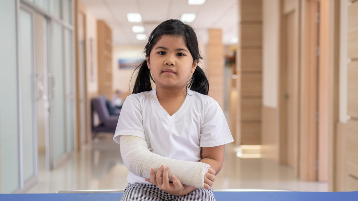 Asian girl treatment in hospital lying on the bed hurting with broken arm back from surgery.