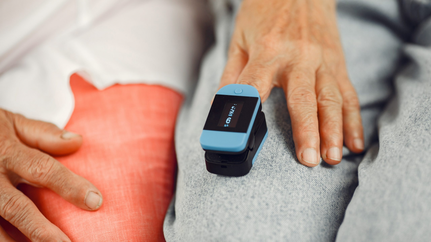 Doctor puts a heart rate monitor on a patient finger. Man holds woman's hand.