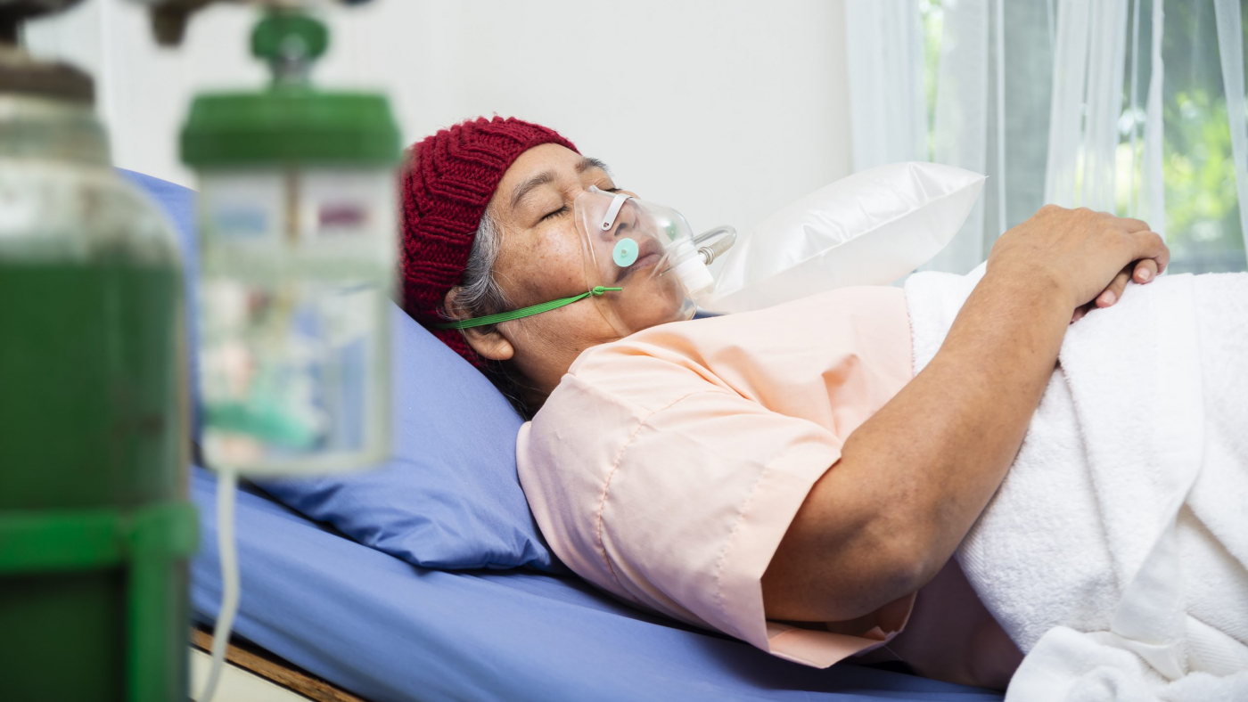 Asian elderly woman wearing wool hat with oxygen mask to breathing while  lying on patient bed, senior female medical and healthcare concept